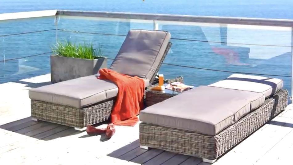 To grå solsenger i rotting med bord imellom på balkong med utsikt mot vann