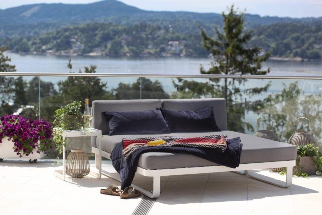 Sjeselong i hvit aluminium med grå puter på terrasse med fantastisk utsikt
