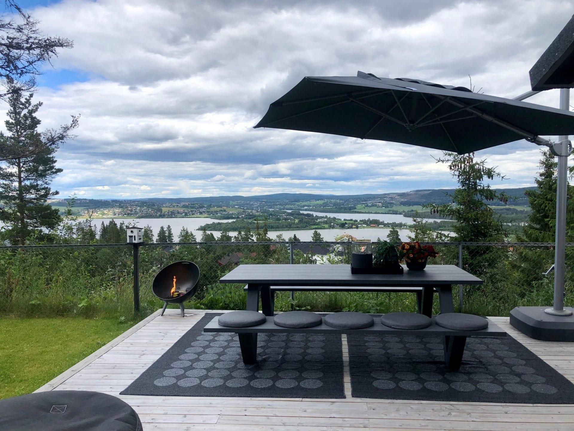 Roterende parasoll i grått farget stoff ved siden av hagebenk og hagebord i hage med flott utsikt