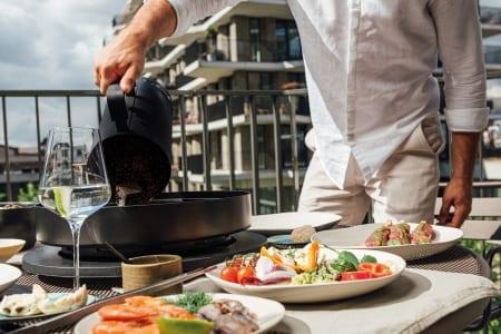 Man tilbereder måltid med OFYR Tablo bordgrill