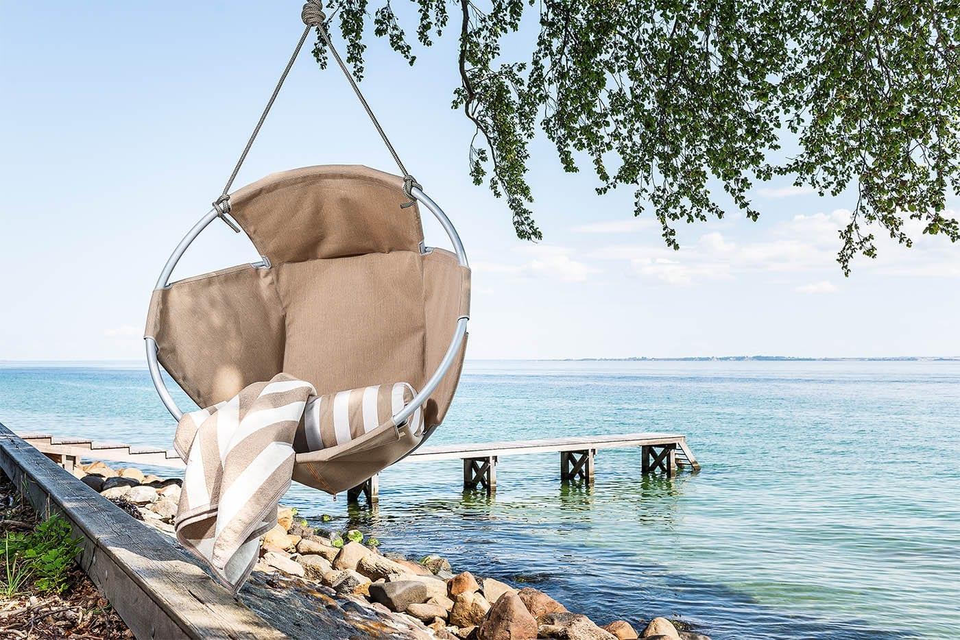 Cocoon-hang-chair-taupe-henger-i-et-tre-ved-vakkert-hav Hagemøbler og utemøbler - Fine design