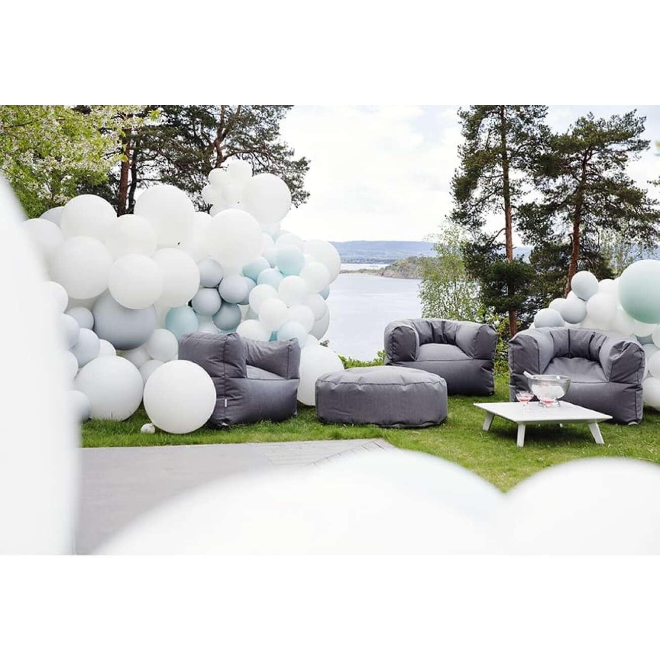 Arm strong stoler fra TRIMM Copenhagen med ballonger på uteplass ved sjøen