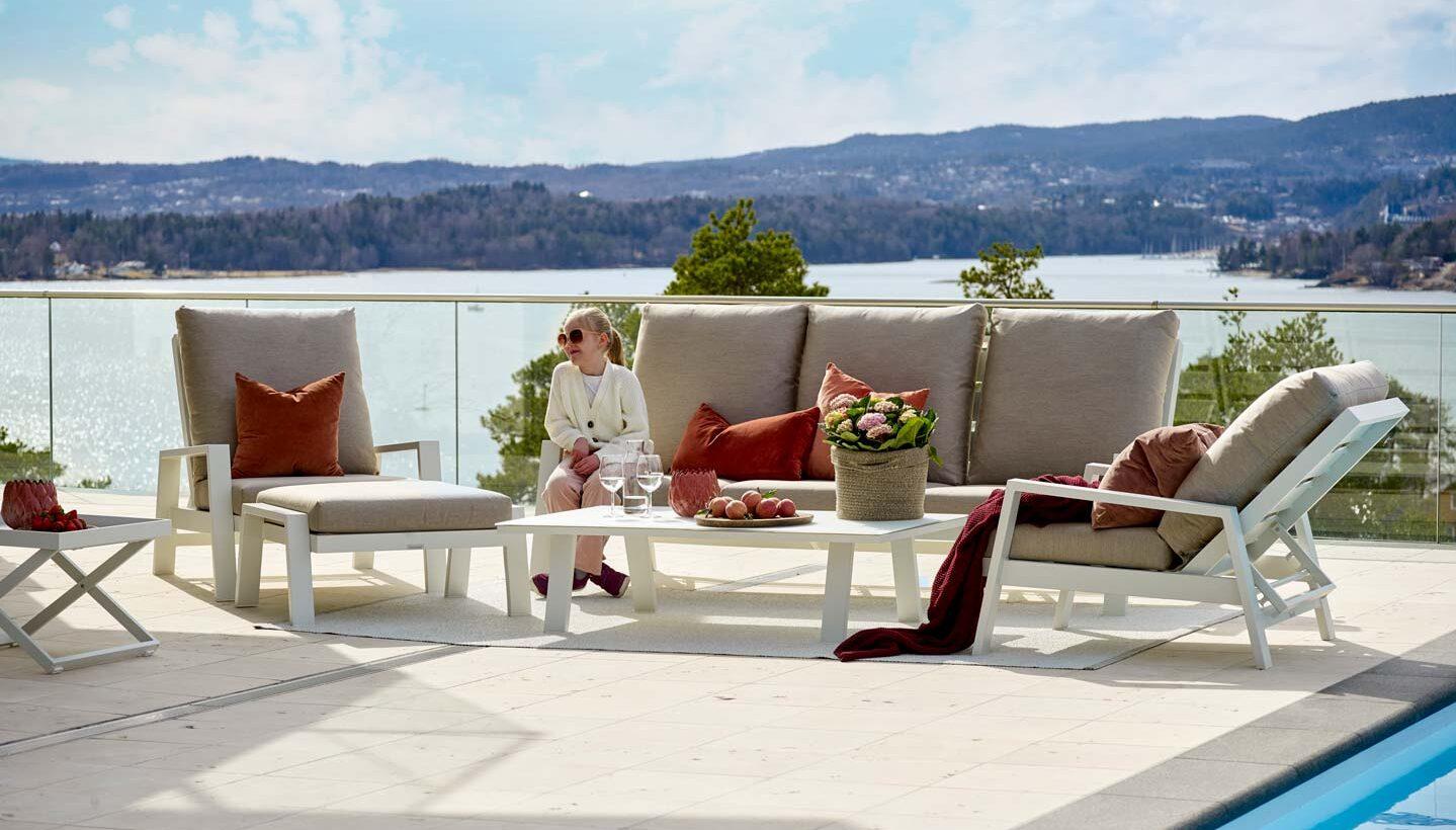 En smilende jente sitter i en hvit sofagruppe med beige puter og hvitt sofabord