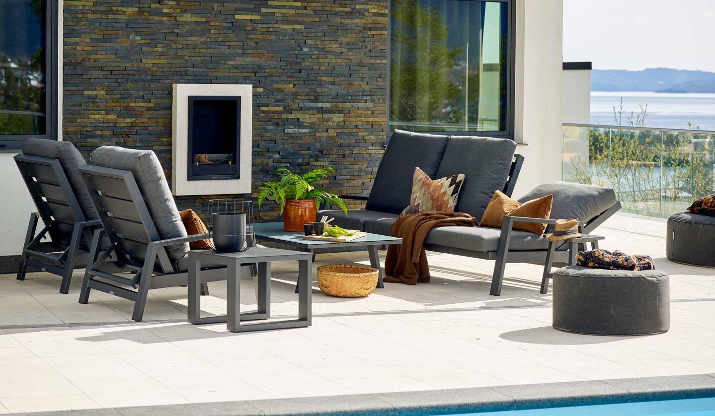Grå sittegruppe med grå puter, der ryggen kan legges ned for å brukes som solseng.