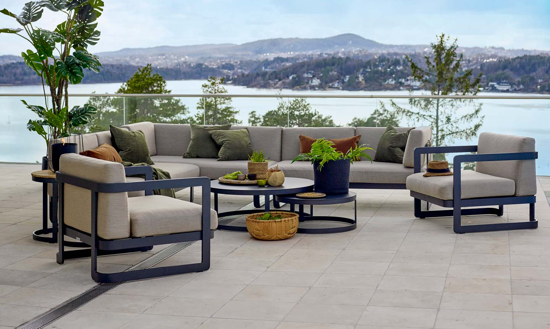 Grå/beige sittegruppe med sorte aluminiomsben med sort sofabord foran en stemningsfull fjordutsikt