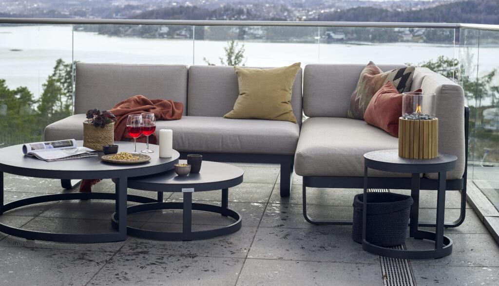 Utesofa med grå puter og sort aluminiumsramme foran en fantastisk utsikt og med stemningsfult tilbehør