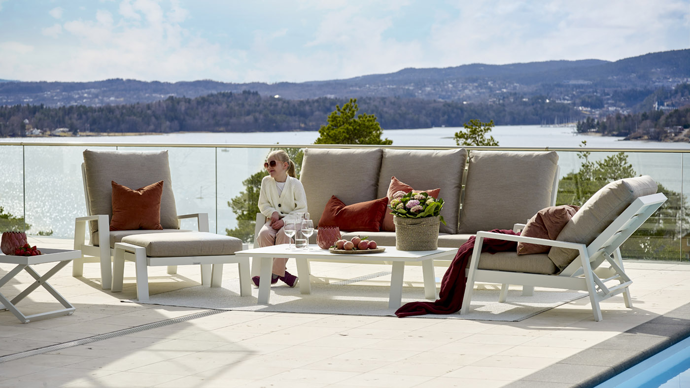 Jente med solbriller sitter på en Fine Design hagesofa på en flott veranda