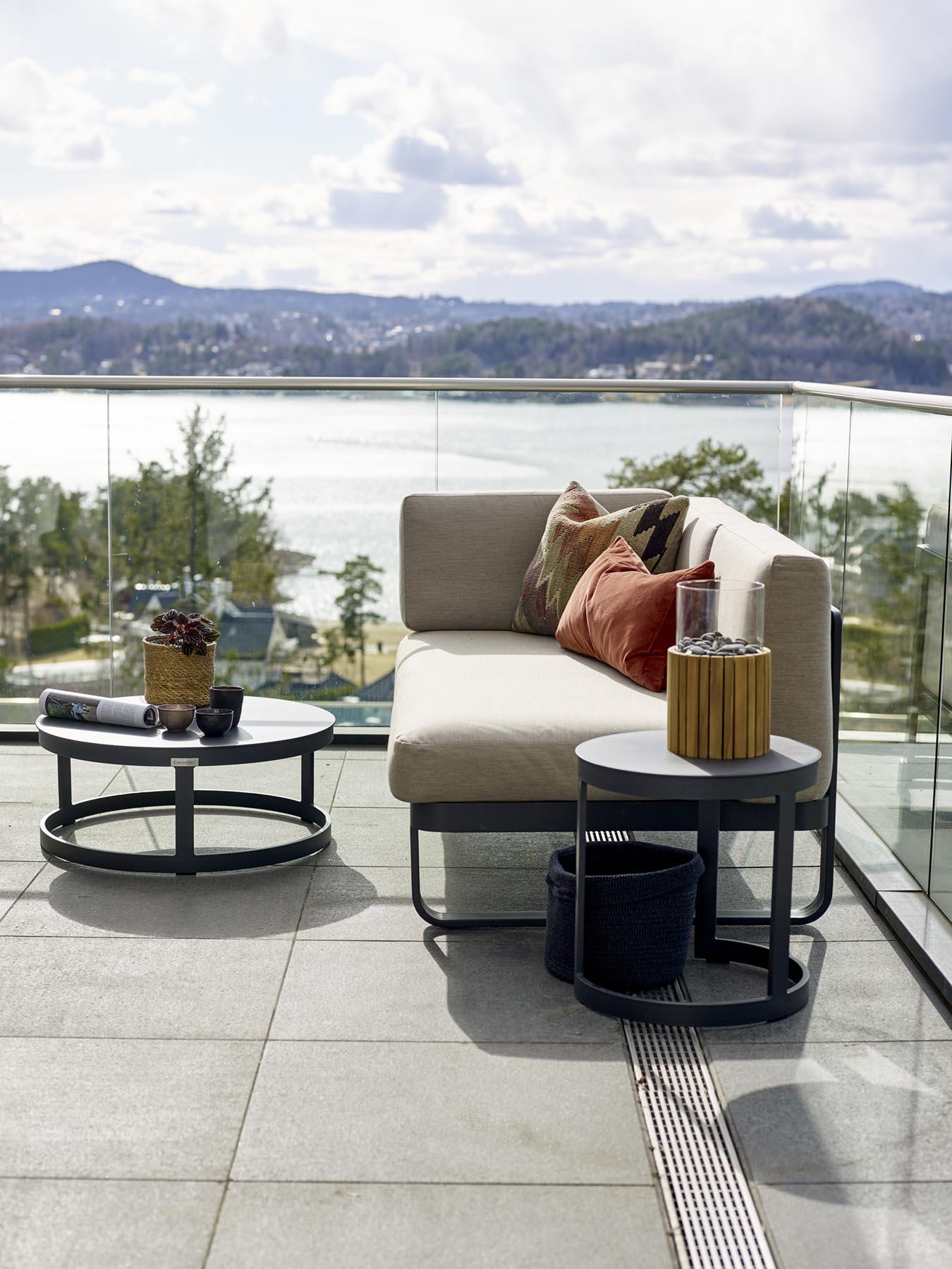 Liten modulsofa med rundt bord i sola på flott terrasse med fantastisk utsikt