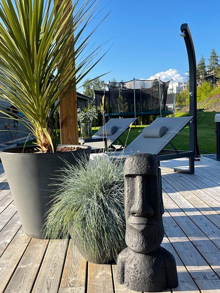 Figur på terrasse ved siden av planter og med solsenger i bakgrunnen copy